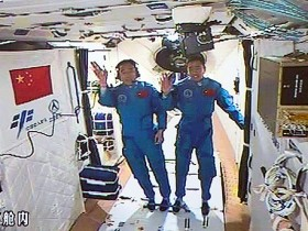 two taikonauts salute in Tiangong2 after Shenzhou11's docking with the lab