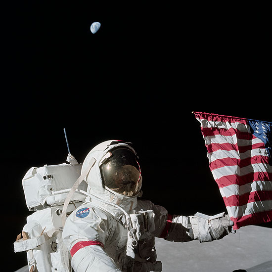 "Apollo 17 commander Eugene A. Cernan is holding the lower corner of the American flag during the mission's first EVA, December 12, 1972. Photograph by Harrison J. ""Jack"" Schmitt"